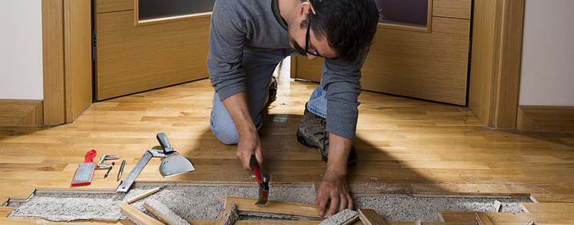 Worker disassembling wooden floor after water damage